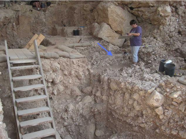 Zdjęcie z wykopalisk w jaskini Qesem (strzałka wskazuje palenisko). Fot. Instytut Weizmanna